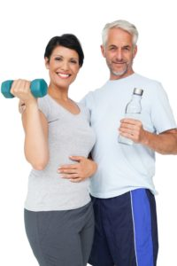 Portrait of a happy fit couple with dumbbell and water bottle white background